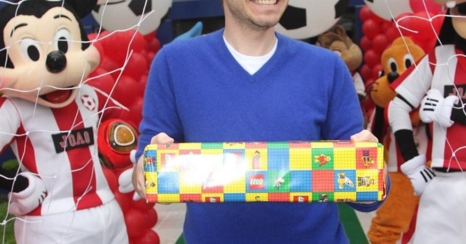 07.nov.2013 - Tiago Leifert posa com o presente no aniversário do filho de Caio Ribeiro