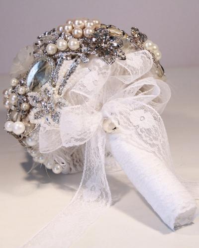 Buquê de broches com haste envolta por fita de cetim e renda e a aplicação de um pequeno relicário no laço