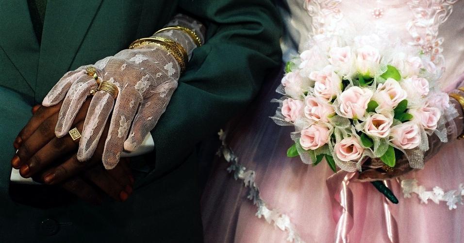Buquê delicado com tecido envolvendo as flores e hastes envoltas por uma fita de cetim rosa. O tecido ainda combina com a luva da noiva