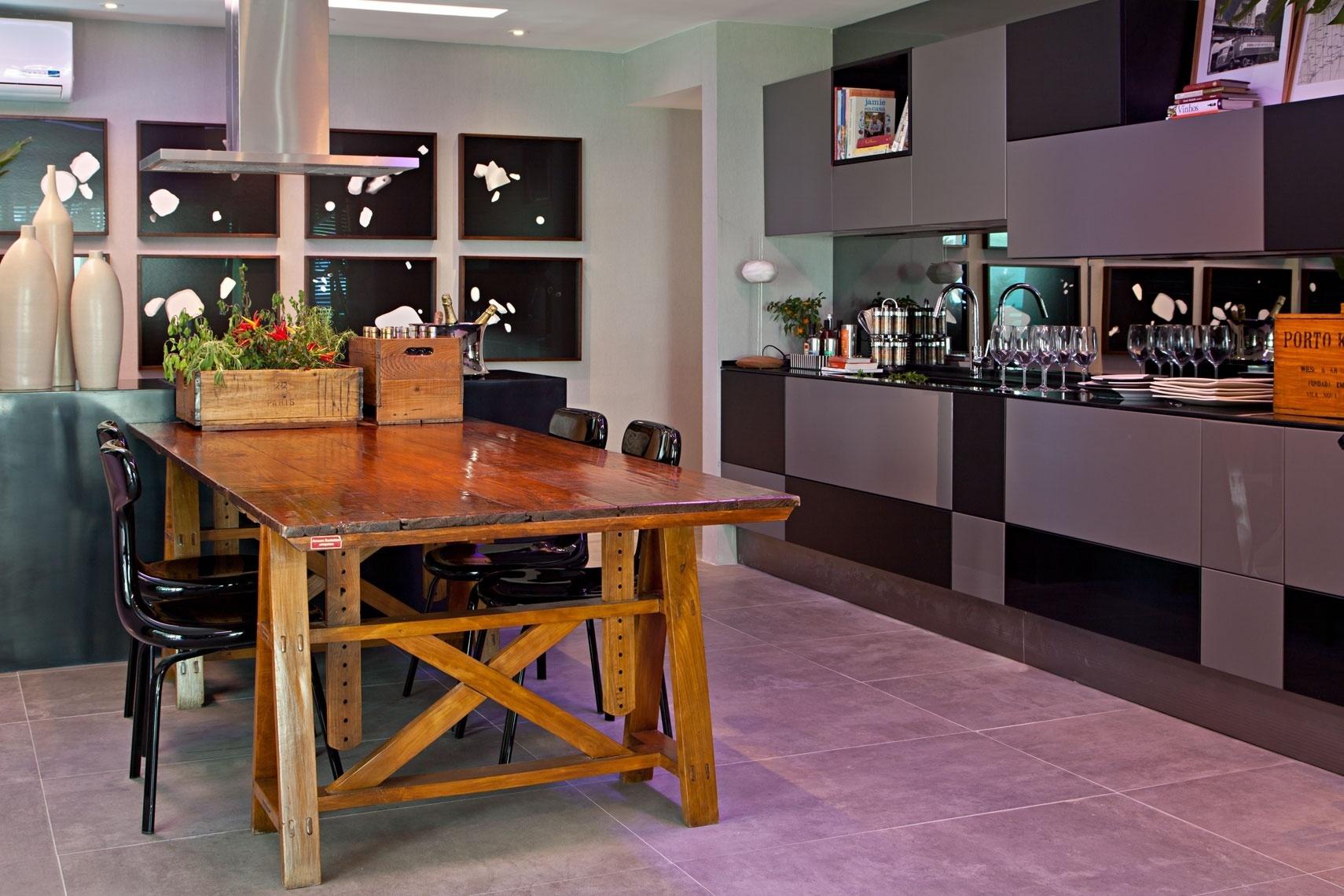 O Living do Jovem Empresário, criado por Erick Figueira de Mello, possui também uma área dedicada à cozinha. Nessa porção do ambiente, a conformação decorativa é mantida: base cinzenta e um elemento