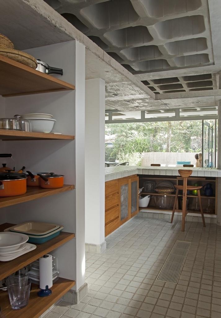 Na cozinha (17 m²) da casa de praia, projetada por Gustavo Calazans, todos os nichos foram aproveitados com marcenaria e dão suporte a objetos. A bancada também organiza as funções: do outro lado, no estar, a bagunça fica escondida sob o balcão que assume o papel de copa e bar. Para aumentar as áreas de apoio na cozinha, o perímetro do espaço é contornado com prateleiras de concreto