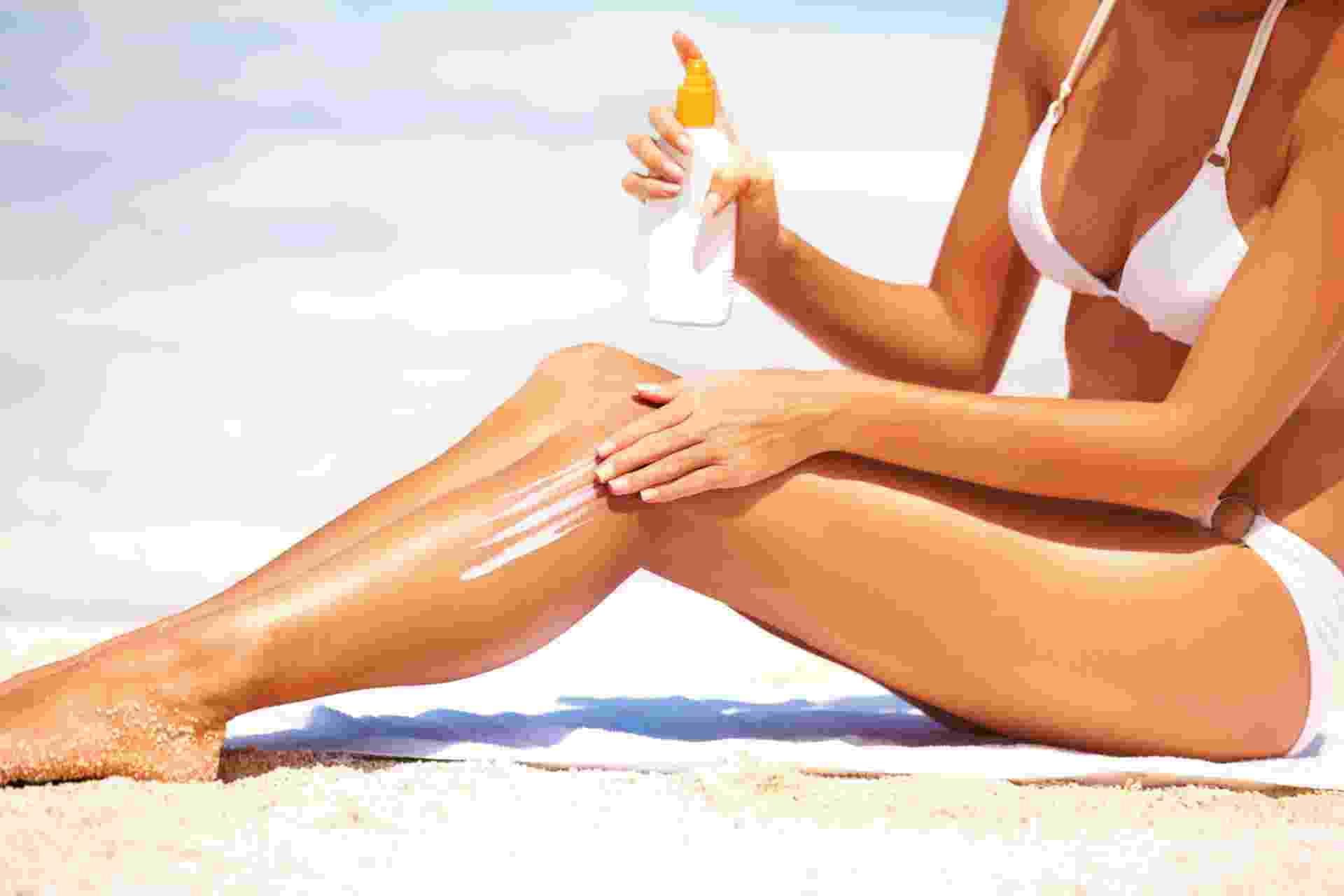Mulher aplicando protetor solar na praia - Thinkstock