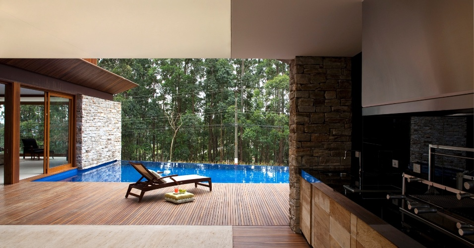 A área da churrasqueira é um eixo de convivência importante na casa M.A.N., com projeto do escritório Gálvez & Marton Arquitetura. A churrasqueira da Império Grill é acompanhada por móvel de madeira de demolição e pia com tampo em granito preto absoluto (Pedras Ipiranga). A residência fica em Barueri, São Paulo