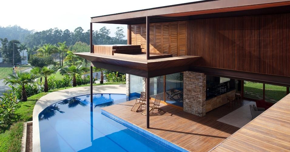 """A piscina em """"L"""" é revestida internamente por pastilhas de vidro Vitrocolori. O tanque, voltado ao norte, tem a água aquecida pelo sol, naturalmente. O posicionamento da área de lazer, com churrasqueira, deck e academia aproveita ao máximo a luz natural. O piso que contorna a piscina é de fulget (granilite lavado) antiderrapante. Uma passagem subaquática serve de acesso ao interior da sauna (atrás da academia). A casa M.A.N. fica em Barueri (SP) e tem projeto da Gálvez & Marton Arquitetura"""