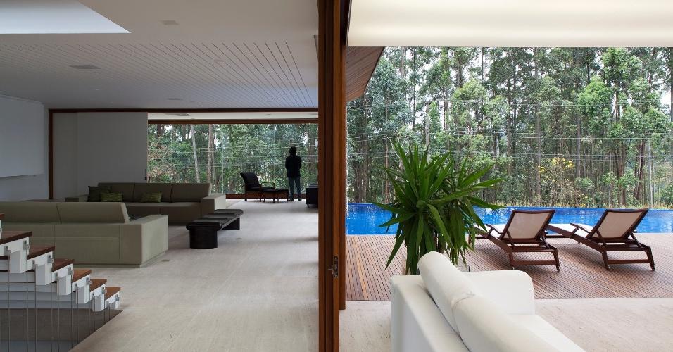 Na casa M.A.N., do escritório Gálvez & Marton Arquitetura, é fácil observar a integração entre dentro/fora: uma folha de vidro instalada nas portas de correr é a única separação entre a piscina e o interior dos estares. Todo o entorno é verde com eucaliptos e a entrada de luz natural através da cobertura de vidro produz a sensação de que a casa foi
