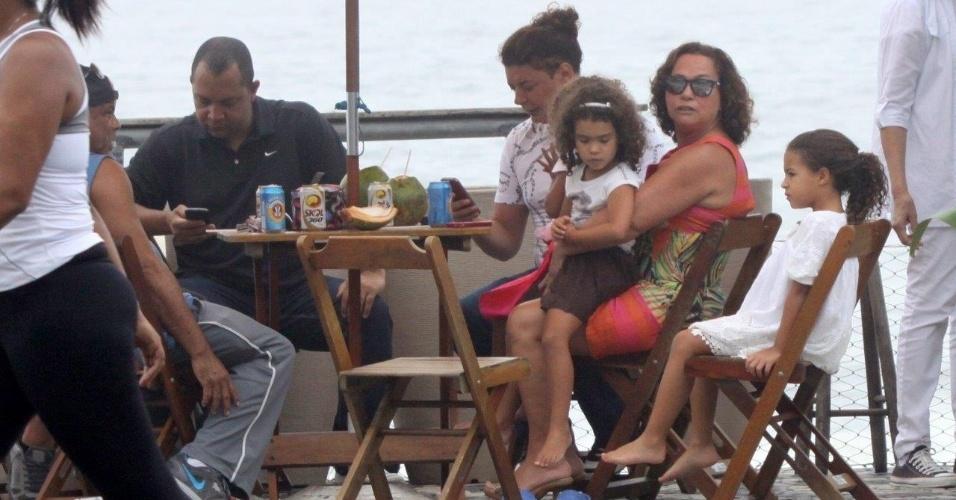 24.nov.2013 - Dona Sônia, mãe de Ronaldo, sentada em uma mesa em um quiosque no calçadão do Leblon com as netas, Maria Beatriz e Maria Sophia. O promoter David Brazil e o pai de Ronaldo, Nélio Nazário também estavam presentes