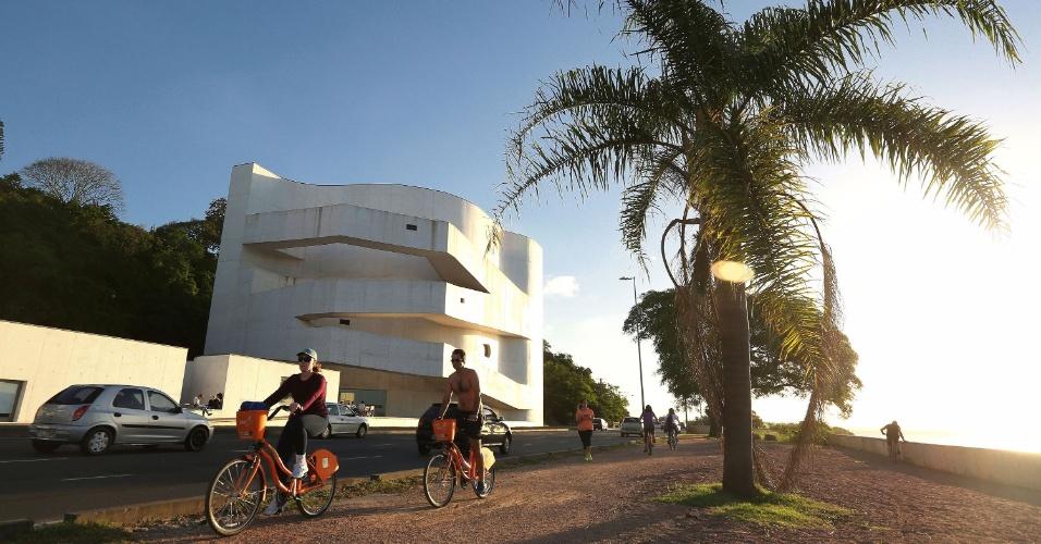 Ciclistas passeiam na orla do rio Guaíba, em Porto Alegre (RS). Ao fundo, museu Iberê Camargo, um dos cartões-postais da cidade
