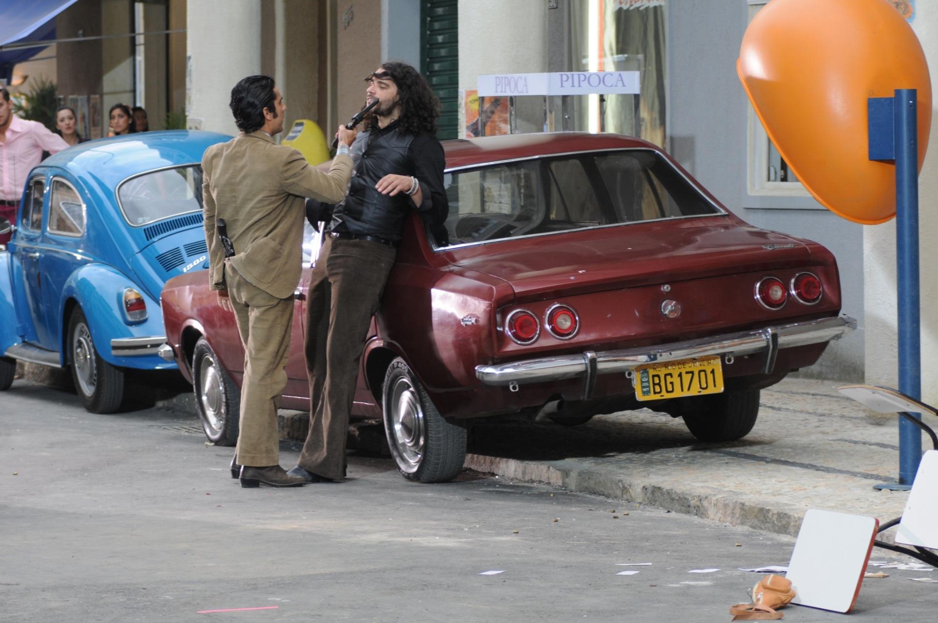 Em cena que Veludo (Guilherme Winter) atira em Otávio (Felipe Cardoso),  aparecem Opala 78-80 (preto) e 75-79 (caramelo e vinho), além de  Fusca 1500 (meados dos anos 70)