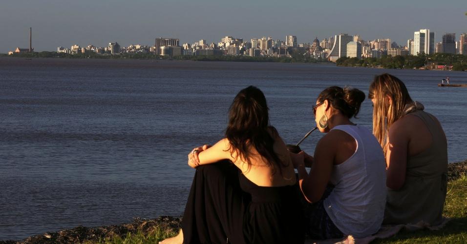 Jovens descansam no gramado às margens do rio Guaíba, em Porto Alegre (RS), onde assistem ao pôr-do-sol. Cena faz parte do cotidiano gaúcho