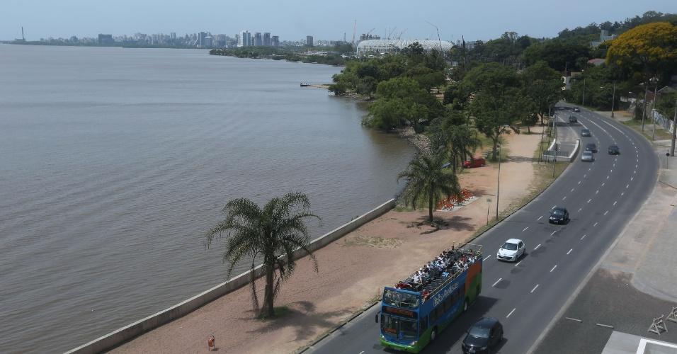 Ônibus da Linha Turismo, de Porto Alegre (RS), circula pela orla do rio Guaíba. Ao fundo, Estádio Beira Rio