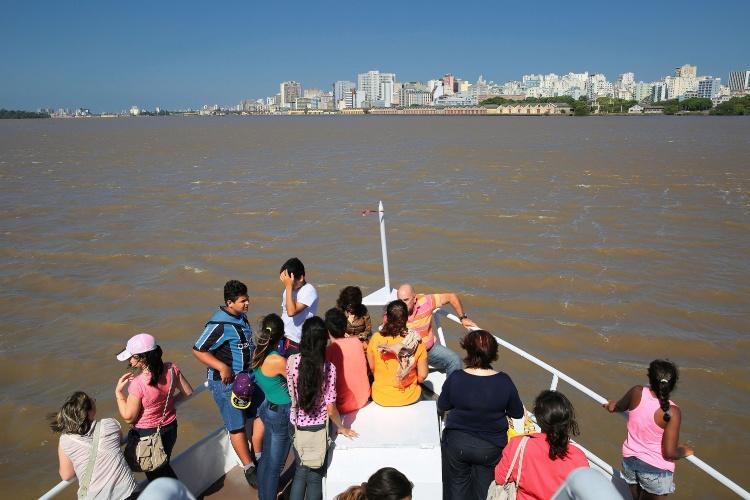 Turistas passeiam de barco pelo rio Guaíba. Percurso passa por entre as ilhas do delta do rio e a paisagem é de muito verde em contraste com os prédios modernos da capital gaúcha Porto Alegre (RS)