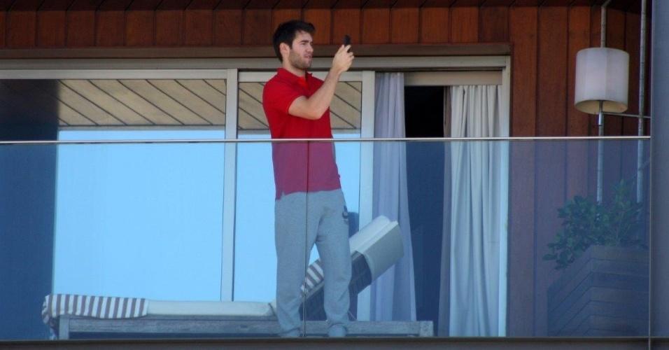 """28.nov.2013 - Usando uma camisa do Brasil, o ator Joshua Bowman, da serie """"Revenge"""", fotografa a paisagem do Rio de Janeiro da varanda de seu quarto em um hotel em Ipanema"""