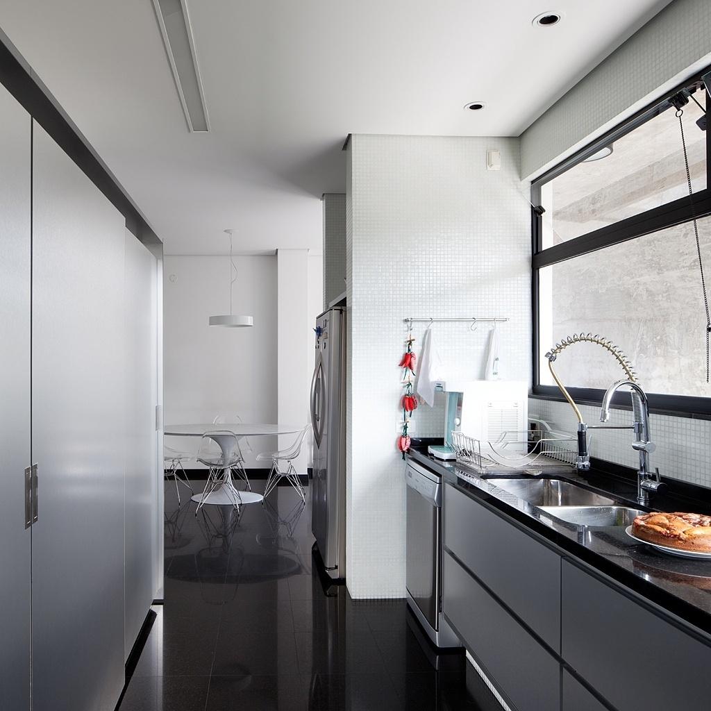 A cozinha foi totalmente remodelada e teve o sistema hidráulico substituído durante a reforma assinada pelo escritório Stuchi&Leite Projetos. No ambiente, uma das paredes foi ocupada por armários e a outra pela bancada da pia e por janelas. Ao fundo, há um espaço dedicado às refeições com mesa Saarinen. A Casa G+A tem projeto original dos arquitetos Carlos Lemos e Eduardo Corona
