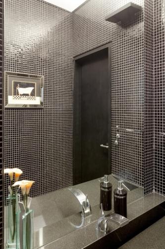 O lavabo da Casa G+A, projetada pelos arquitetos Lemos e Corona e reformada pelo escritório Stuchi&Leite Projetos, ganhou novos revestimentos: pastilhas pretas nas paredes e bancada e cuba em granito cinza concedendo um clima sóbrio ao espaço
