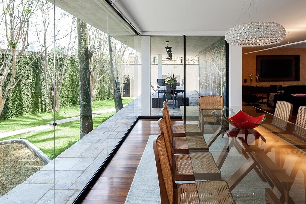 O uso do vidro integra e delimita os espaços da Casa G+A, que tem projeto original dos arquitetos Carlos Lemos e Eduardo Corona e reforma assinada por Stuchi&Leite Projetos. A relação franca e aberta interior/exterior se destaca na sala de jantar, na varanda e no estar, todos voltados para o jardim