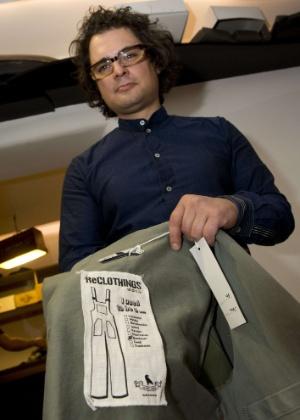 O estilista alemão Daniel Kroh mostra a etiqueta de uma de suas criações no ateliê e showroom de sua marca ReClothings, em Berlim, que trabalha exclusivamente com peças feitas a partir de roupas usadas - John Macdougall/AFP