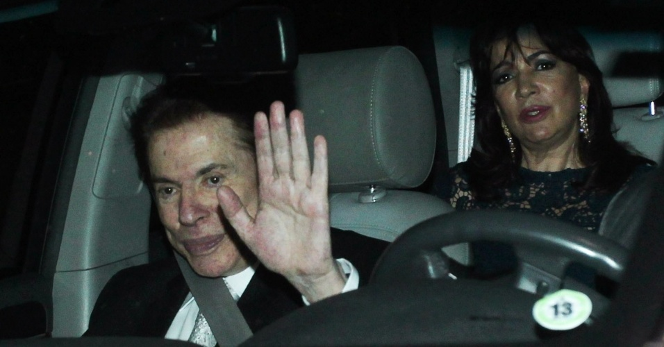6.dez.2013 - Silvio Santos acena para a imprensa ao chegar no casamento da filha