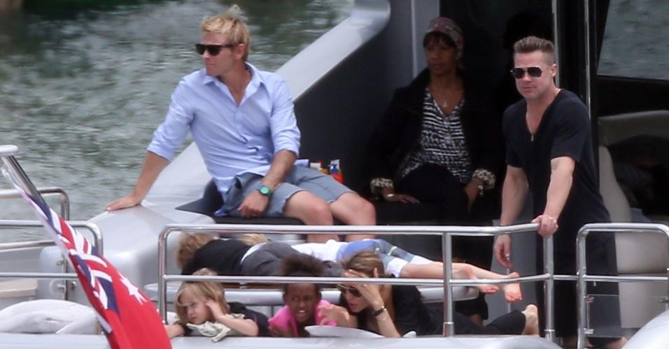 3.dez.2013 - Angelina Jolie conversa com Zahara e Vivienne, enquanto Brad Pitt observa. Ao fundo, Shiloh e Knox descansa deitados em uma mesa