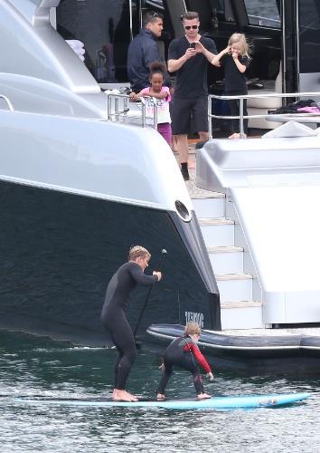 3.dez.2013 - Ao lado das filhas Zahara e Vivienne, Brad Pitt fotografa o filho Knox fazendo stand up paddle em Sydney, na Australia