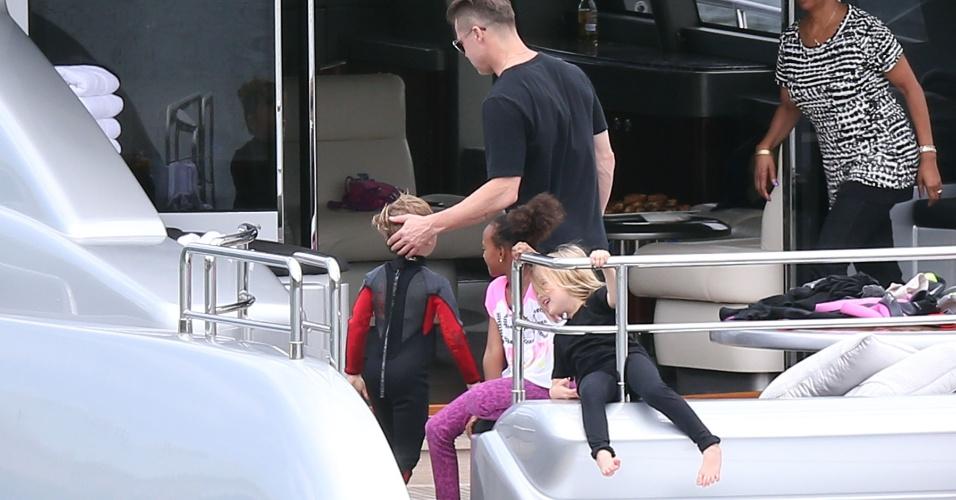 3.dez.2013 - Brad Pitt parabeniza o filho Knox após o menino fazer tand up paddle em Sydney, na Australia. Também na foto, Zahara e Vivienne