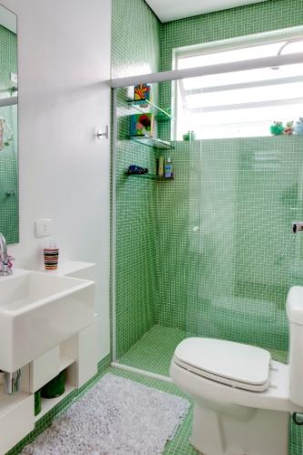 No banheiro projetado pela arquiteta Graziela Arruda, as miúdas pastilhas na cor verde foram assentadas em toda extensão do box e do piso do ambiente. O revestimento vibrante deixa o espaço