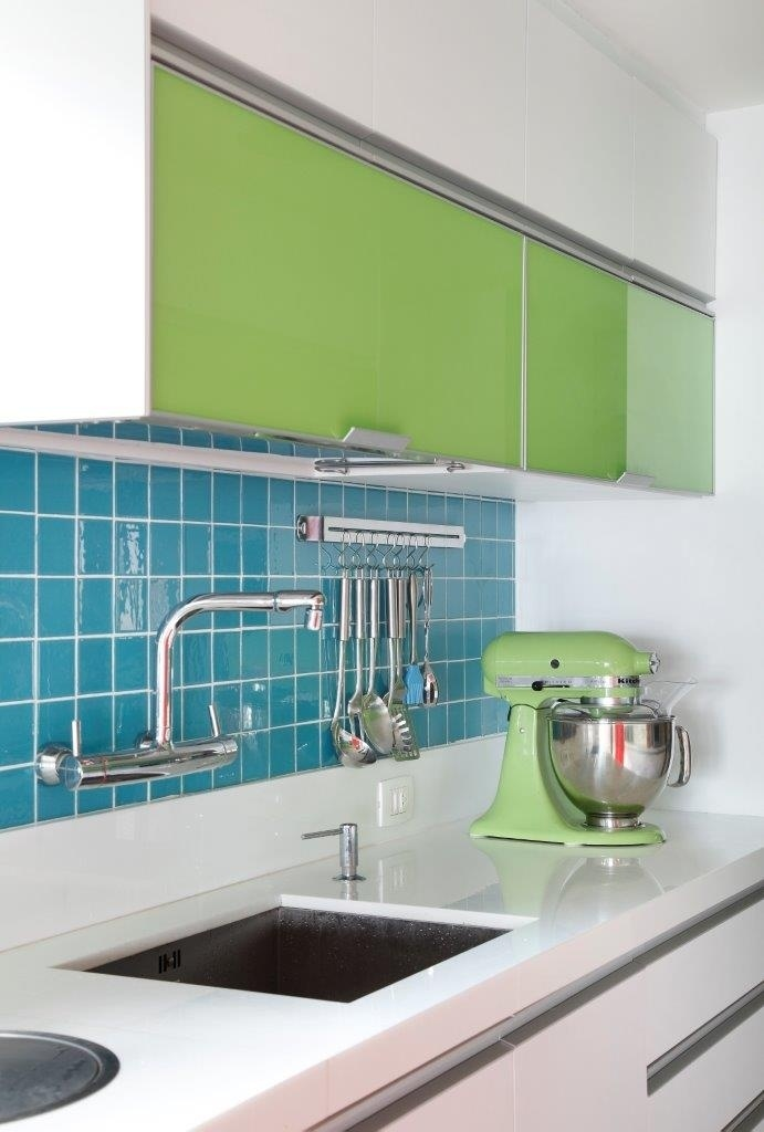 Os azulejos azuis em padronagem pequena foram usados pontualmente e combinados aos armários com portas em um tom de verde vibrante. O comjunto dá um ar alegre à cozinha decorada pela dupla de arquitetas Carmen Zaccaro e Marise Kessel