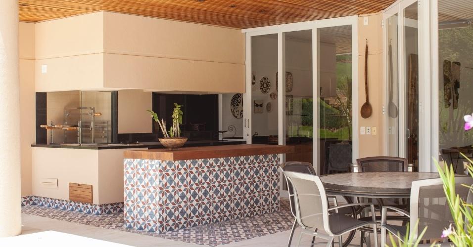 Na varanda da casa de campo projetada pelo Studio Costa Marques, o ladrilho hidráulico não só cobre o piso e demarca a área da churrasqueira, como reveste o balcão com tampo grosso de madeira cumaru