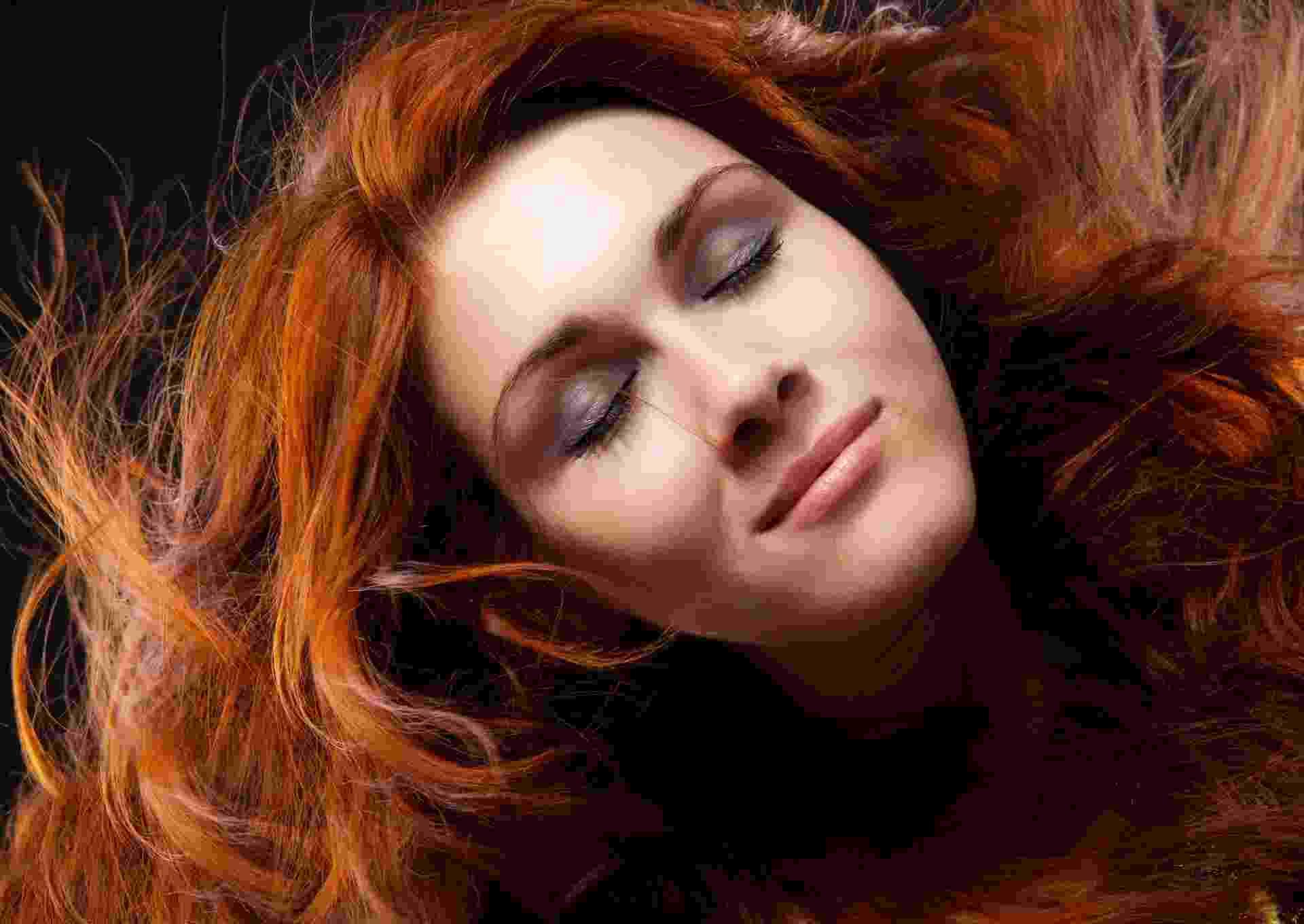 Mulher com os cabelos tingidos de ruivo - Thinkstock