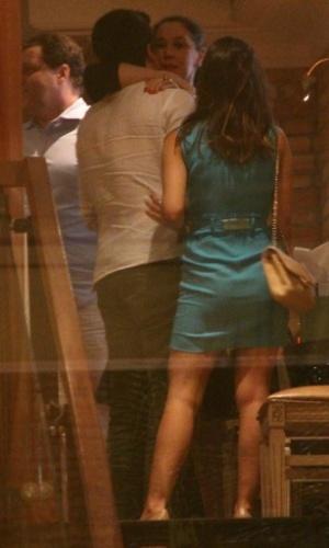 23.dez.2013 - Claudia Raia beija o filho Enzo, ao lado da namorada, Rafaella Rique, no seu aniversário de 47 anos, em um restaurante na zona oeste do Rio