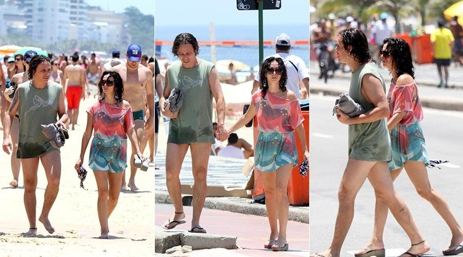 28.dez.2013 - Claudia Ohana e o namorado vão à praia de Ipanema, no Rio