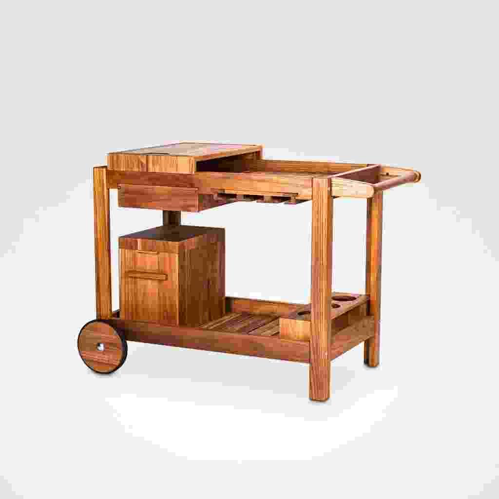 Esse carrinho de serviços, todo confeccionado em madeira teca, conta com tábua de churrasco móvel, gaveta, porta taças, porta garrafas e um isopor para gelo/cerveja. As duas rodas facilitam o transporte. À venda por R$ 3.557 na Teakstore (www.teakstore.com.br) - Divulgação