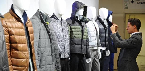 """Visitante fotografa casacos expostos na feira de moda masculina Pitti Uomo, em Florença, na Itália (07/01/2014) - Maurizio Degl""""Innocenti/EFE"""
