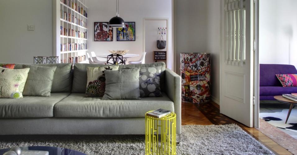 Com um sofá de linho cinza e um tapete de mesma tonalidade (ambos da Novo Ambiente), as arquitetas Roberta Moura, Paula Faria e Luciana Mambrini garantiram uma base neutra à sala de estar do apartamento no bairro do Leblon, Rio de Janeiro (RJ).  A mesa de apoio Kub (Poeira), feita em metal com pintura amarela, pontua com cor o cômodo