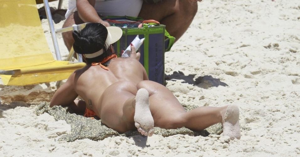 Dani Sperle usa fio dental para retocar o bronzeado em praia carioca