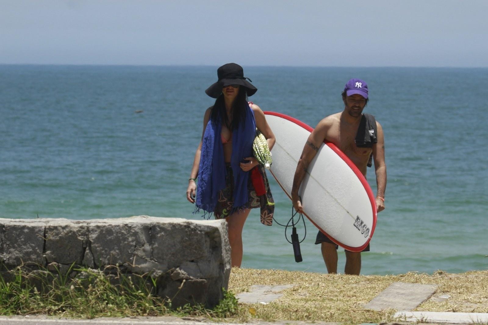 10.jan.2014 - Grávida, Alinne Moraes esconde a barriga em dia de praia