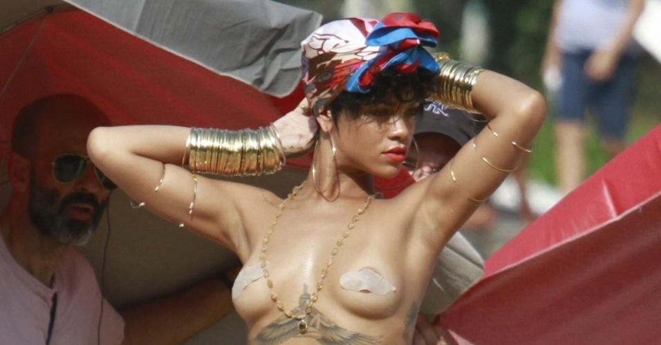 """13.jan.2014 - Em Angra dos Reis, no Rio de Janeiro, Rihanna fotografa para a revista """"Vogue Brasil"""" com os seios de fora. Ela cobre os mamilos com filha adesiva"""