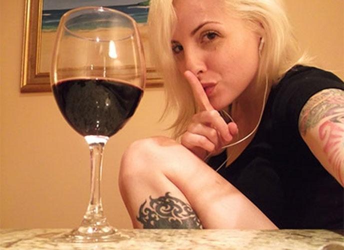 Como outros participantes, Clara posa para foto com vinho servido no quarto do confinamento