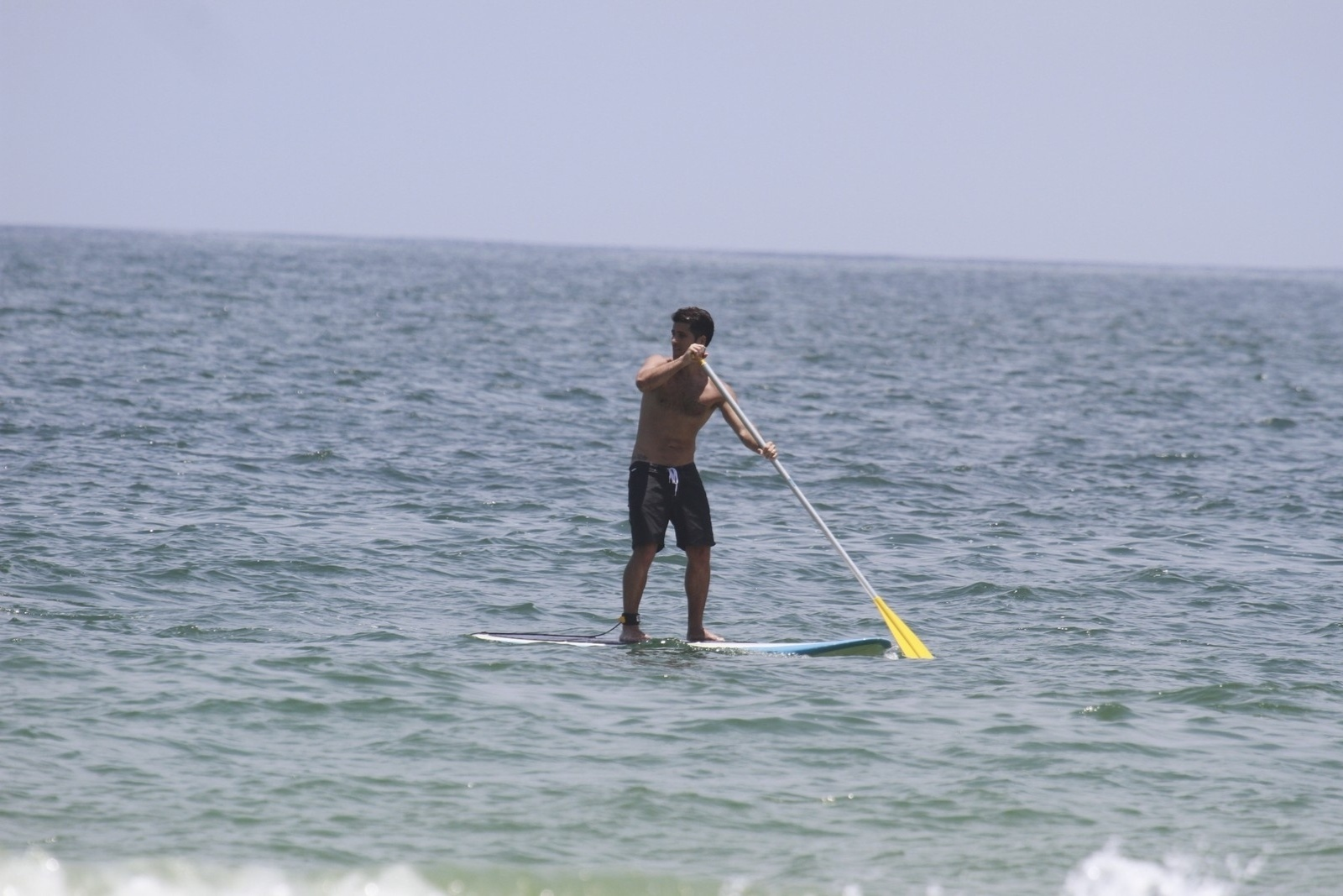 16.jan.2014 - Bruno Gagliasso pratica stand up paddle com Giovanna Ewbank de plateia
