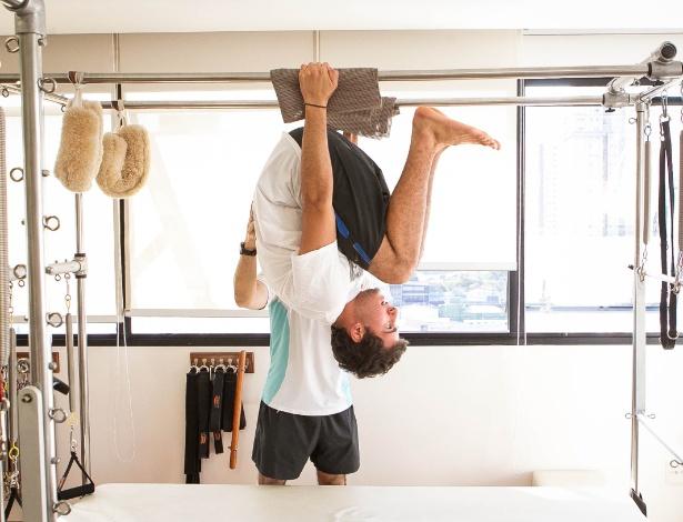 André Pinho fazendo um dos exercícios de pilates, sob orientação do professor Alexandre Ohl - Rodrigo Capote/UOL