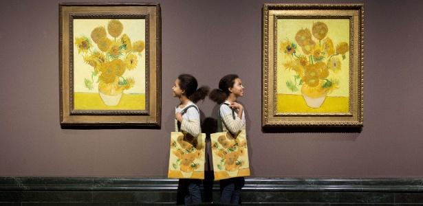 """As gêmeas Ella (esq.) e Eva posam com as duas versões da pintura """"Os Girassóis"""", de Vincent van Gogh, expostas na National Gallery de Londres - Leon Neal/AFP"""