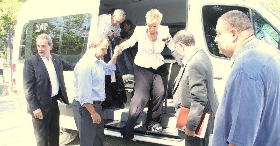 3.fev.2014 - Xuxa participou da inauguração de uma escola com o nome de Hebe Camargo, na manhã dessa segunda-feira (3), no Rio de Janeiro. Usando uma bota ortopédica, a apresentadora precisou de ajuda para descer de uma van