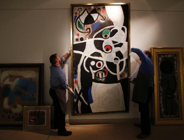 """19.dez.2013 - Quadro """"Mulheres e Flores"""", de Miró, parte da coleção de 85 telas cuja venda foi anulada, é manuseado em casa de leilão - Lefteris Pitarakis/AFP"""