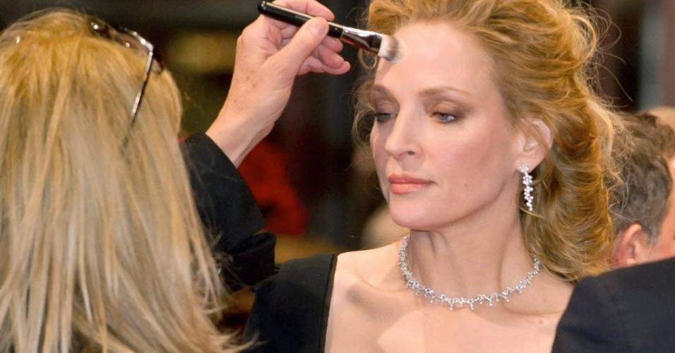 09.fev.2014 - Uma Thurman retoca maquiagem ao chegar para estreia da versão mais longa de