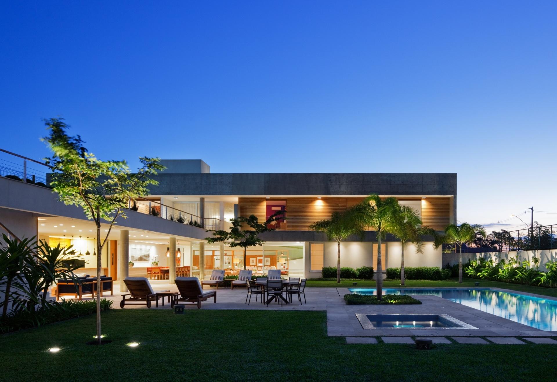 Ao anoitecer, a Casa FG, projetada pelo escritório Reinach Mendonça Arquitetos Associados, se enche de luz tanto nos interiores quanto na fachada e nos jardins, incluindo a piscina