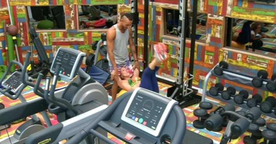 12.fev.2014 - Em posição inusitada, Valter Slim ajuda Aline a se exercitar na academia