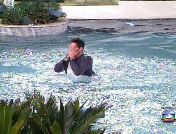 18.fev.2014 - Para comemorar a permanência do programa, Diego se joga na piscina