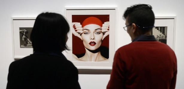 """Pessoas observam imagens expostas na exposição """"Papel brilhante, um século de fotografia de moda da Condé Nast"""" - AFP"""