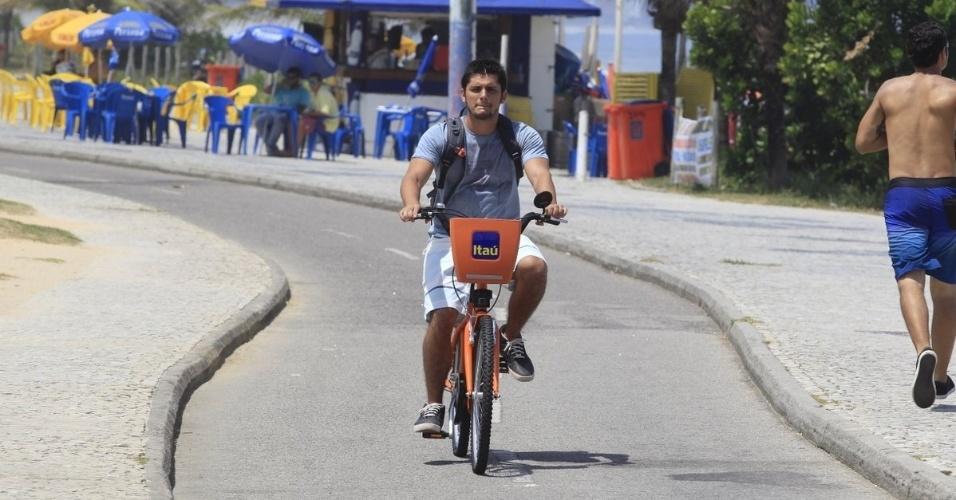 28.fev.2014- Bruno Gissoni grava cena de André pedalando na praia do Recreio, zona oeste do Rio