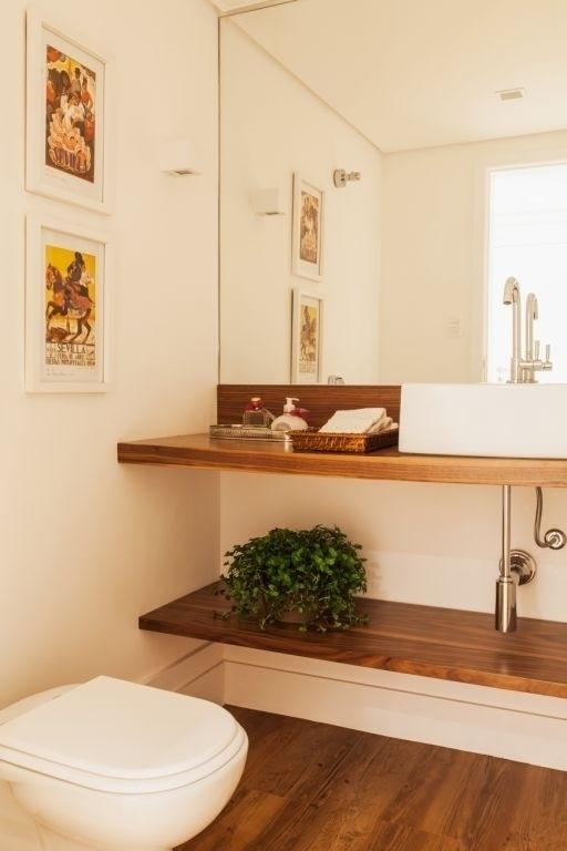 Os quadros na parede se alinham à decoração desse lavabo, assinado pela arquiteta Vivi Cirello. O verde apareceu no vaso de plantas posicionado na prateleira de madeira, logo abaixo da bancada da pia