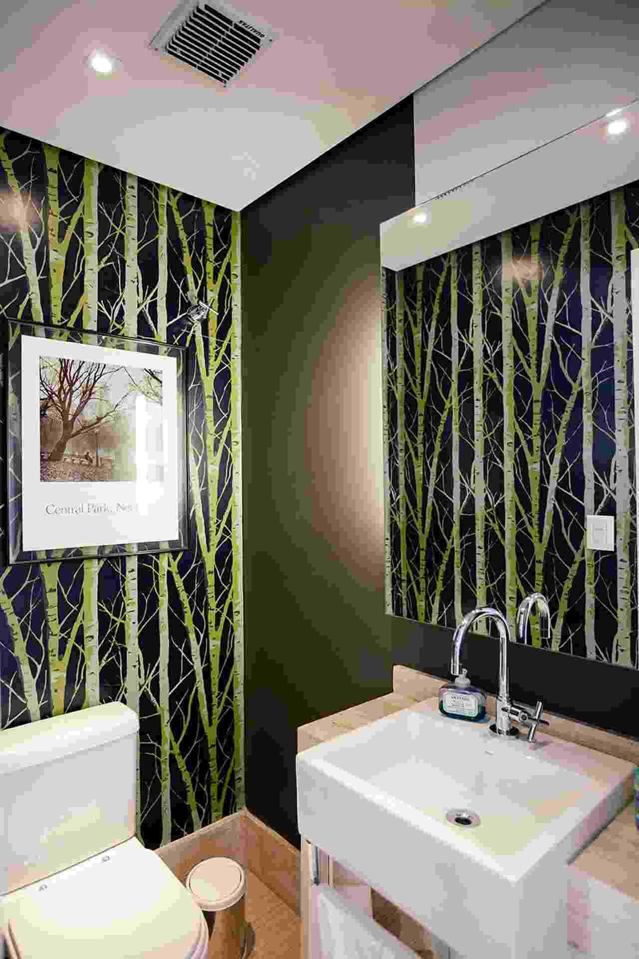 """A decoração ousada deste lavabo, projetado pela arquiteta Flavia Machado, foi ditada pelo revestimento de parte das paredes com o papel chamativo e cheio de informação. Como o ambiente é de curta permanência, o recurso funciona perfeitamente e não cansa. A padronagem ainda cria um """"quadro"""" ao ser refletida pelo espelho, instalado estrategicamente em uma parede neutra e """"chapada"""" - Divulgação"""